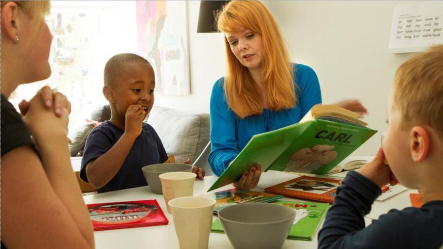 En voksne læser højt for to børn